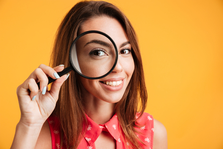 Foto de Close up of young cheerful brunette woman looking through magnifying glass, isolated over yellow background - Imagen libre de derechos