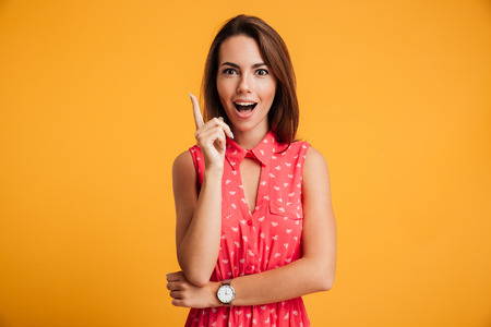 Photo for Close-up portrait of charming young woman in red dress pointing with finger, looking at camera, isolated on yellow background - Royalty Free Image
