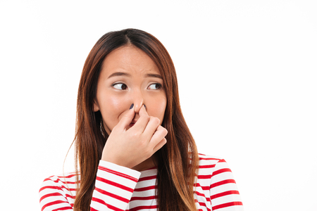 Photo pour Portrait of a young disgusted asian woman blocking her nose with fingers and looking away isolated over white background - image libre de droit