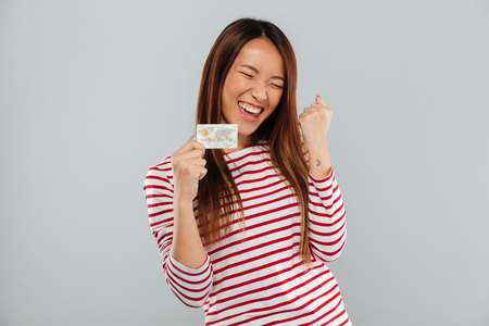 Photo pour Happy asian woman in sweater rejoice and holding credit card over gray background - image libre de droit