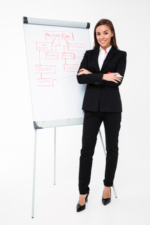 Foto de Image of happy pretty businesswoman isolated over white background near business plan and showing it. Looking camera. - Imagen libre de derechos