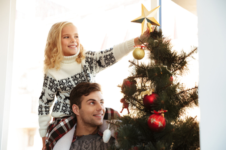 Photo pour Young man with his daughter on his shoulders helping her decorate the Christmas tree - image libre de droit