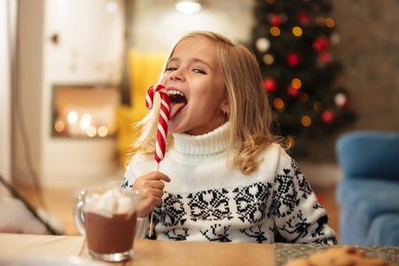 Foto de Close-up photo of funny little girl licks candy cane, looking at camera - Imagen libre de derechos