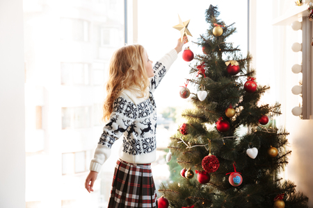 Photo for Cute little girl in knitted sweater placing star on the top of Christmas tree - Royalty Free Image