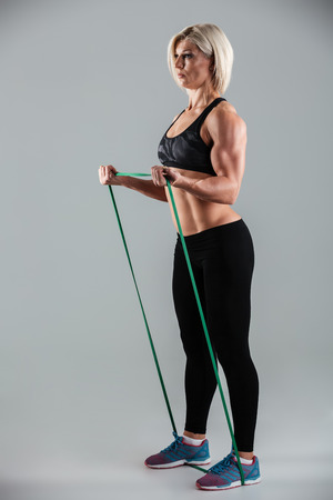 Photo pour Full length photo of strong sports woman exercising with resistance band, looking aside, isolated on white background - image libre de droit