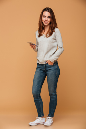 Foto de Full length portrait of smiling beautiful woman in casual wear standing with hand in the pocket, holding smartphone, looking at camera, isolated on beige background - Imagen libre de derechos