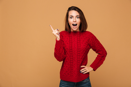 Photo for Happy young woman with opened mouth pointing with finger up, looking at camera, isolated on beige background - Royalty Free Image
