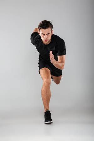 Foto de Photo of strong young sports man running isolated over grey wall background. Looking camera. - Imagen libre de derechos