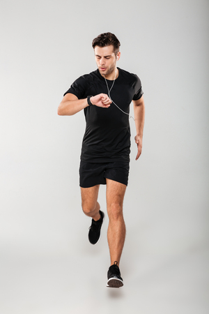 Photo pour Full length portrait of a young fit sportsman in earphones listening to music while running and looking at his wristwatch isolated over gray background - image libre de droit