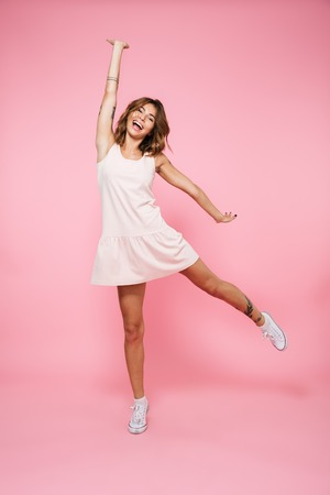 Photo pour Full length portrait of a laughing joyful girl in summer dress jumping with outstretched hand and looking at camera isolated over pink background - image libre de droit