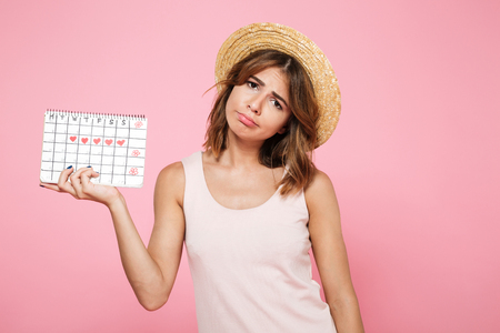 Photo pour Portrait of a sad unhappy girl in summer hat holding her periods calendar and looking at camera isolated over pink background - image libre de droit