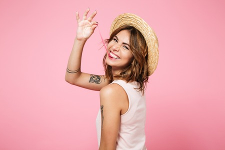 Photo pour Portrait of a funny young girl in summer hat looking at camera over shoulder and playing with chewing gum isolated over pink background - image libre de droit