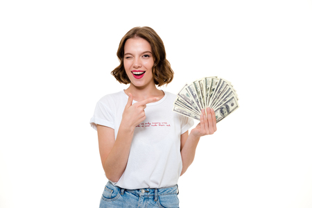 Foto de Portrait of a young playful girl holding bunch of money banknotes while pointing finger at camera and winking isolated over white background - Imagen libre de derechos