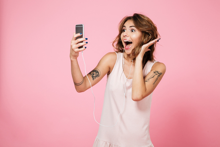 Photo for Portrait of a joyful pretty girl listening music with earphones while standing and taking a selfie with mobile phone isolated over pink background - Royalty Free Image