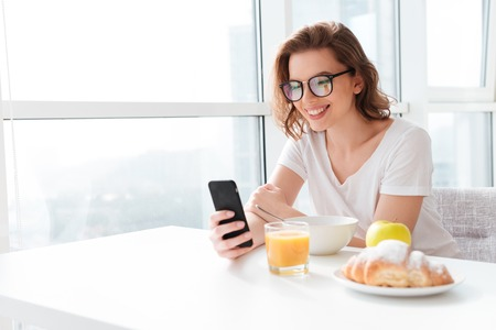 Photo for Photo of cheerful young amazing woman sitting indoors at the table with juice and croissant and corn flakes. Looking aside chatting by mobile phone. - Royalty Free Image