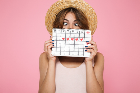 Foto de Portrait of a crazy funny girl in summer hat holding and hiding behind a periods calendar isolated over pink background - Imagen libre de derechos