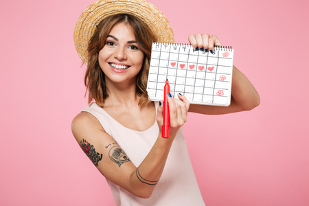 Photo pour Portrait of a smiling pretty girl in summer hat checking her periods according to calendar with a felt-tip pen isolated over pink background - image libre de droit