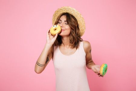 Foto de Portrait of a lovely cute woman in summer hat holding and smelling donuts isolated over pink background - Imagen libre de derechos