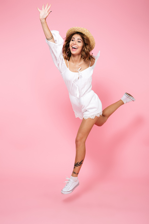 Foto de Full length portrait of a happy pleased girl in summer dress and hat jumping isolated over pink background - Imagen libre de derechos