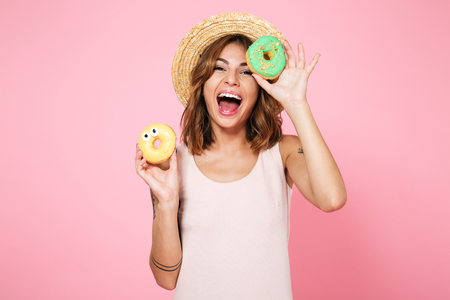 Foto de Portrait of an excited happy woman in summer hat holding donuts isolated over pink background - Imagen libre de derechos