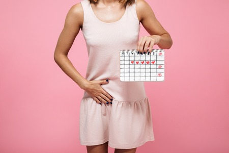 Foto de Cropped image of a young woman in dress holding periods calendar and touching her belly isolated over pink background - Imagen libre de derechos