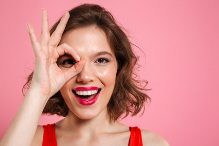 Photo for Close-up portrait of young happy girl with red lips looking at camera through OK sign, isolated on pink background - Royalty Free Image