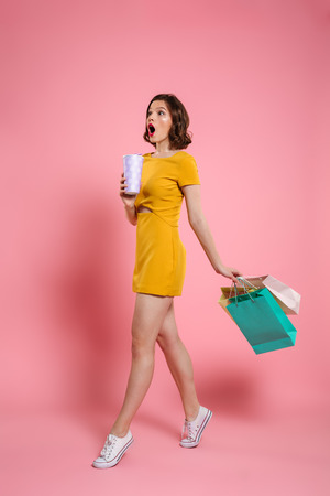 Photo for Full length photo of cute amazed woman in yellow dress holding drink and colorful shopping bags, looking aside, isolated on pink background - Royalty Free Image