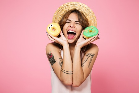 Foto de Portrait of a happy excited girl in summer hat holding donuts and laughing isolated over pink background - Imagen libre de derechos