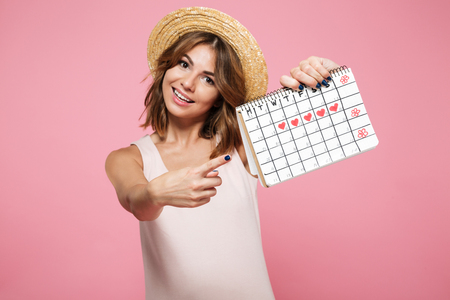 Foto de Portrait of an happy pretty girl in summer hat pointing finger at a calendar with drawn hearts isolated over pink background - Imagen libre de derechos