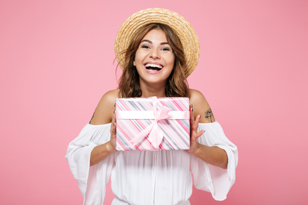 Foto de Portrait of a smiling happy girl in summer hat holding gift box and looking at camera isolated over pink background - Imagen libre de derechos
