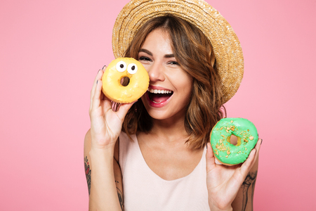 Foto de Close up portrait of a funny smiling woman in summer hat holding donut at her face isolated over pink background - Imagen libre de derechos