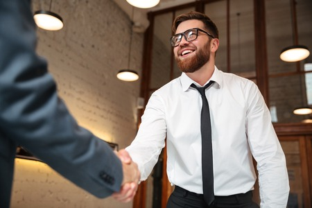 Photo for Close up of two young businessmen shaking hands to make a deal indoors - Royalty Free Image