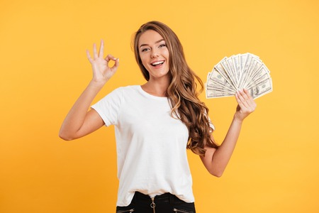 Photo for Portrait of a cheerful smiling girl holding bunch of money banknotes and showing ok gesture isolated over yellow background - Royalty Free Image