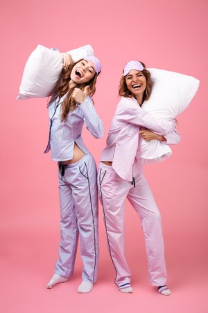 Photo pour Full length portrait of two happy excited girls dressed in pajamas standing and holding pillows isolated over pink background - image libre de droit