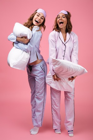 Photo for Full length portrait of two cheerful excited girls dressed in pajamas standing and holding pillows isolated over pink background - Royalty Free Image