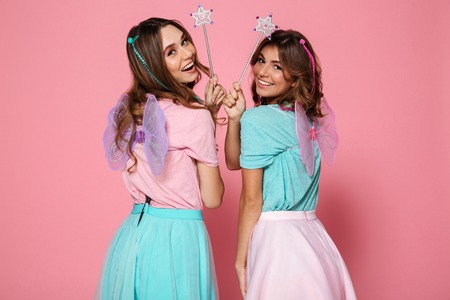 Photo pour Two smiling girls dressed like fairies with wings holding magic wands while looking at camera over shoulder isolated over pink background - image libre de droit