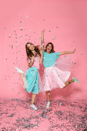 Photo pour Full length portrait of two pretty girls dressed like princess having fun with sequins, isolated over pink background - image libre de droit
