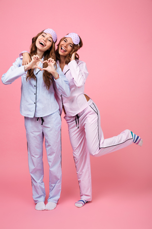 Photo for Photo of pretty two girls friends in pajamas isolated over pink background. Looking camera showing heart love gesture. - Royalty Free Image