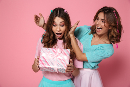 Photo pour Young amazed woman holding present while celebrating birthday with her female friend, isolated over pink background - image libre de droit