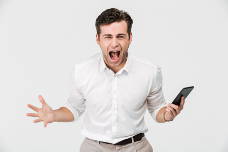Foto de Portrait of a crazy angry man holding mobile phone and shouting isolated over white background - Imagen libre de derechos