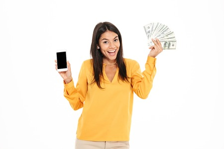 Photo for Portrait of a happy joyful woman holding bunch of money banknotes and showing blank screen mobile phone isolated over white background - Royalty Free Image