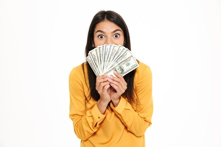 Foto de Portrait of an excited woman holding bunch of money banknotes at her face and looking at camera isolated over white background - Imagen libre de derechos