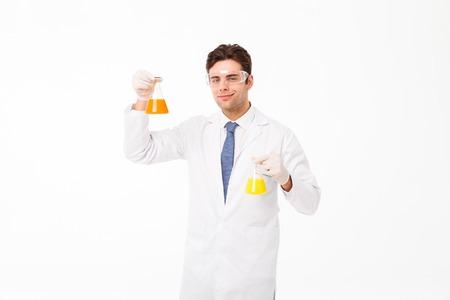 Foto de Portrait of a confident young male scientist dressed in uniform showing test-tubes isolated over white background - Imagen libre de derechos