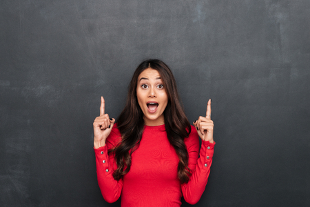 Photo for Image of shocked young beautiful woman standing over dark grey wall chalkboard. Looking camera pointing. - Royalty Free Image
