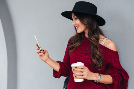 Foto de Portrait of a smiling young asian girl dressed in hat and sweater holding coffee cup while standing and using mobile phone on a city street - Imagen libre de derechos