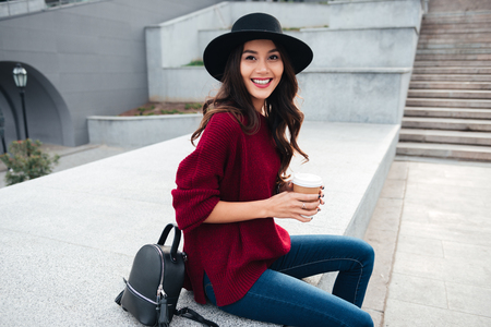 Photo for Portrait of a beautiful smiling asian girl wearing hat and sweater holding coffee cup while sitting on a city street - Royalty Free Image
