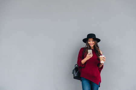 Photo pour Portrait of a happy asian girl dressed in hat and sweater holding coffee cup while standing and using mobile phone on a city street - image libre de droit
