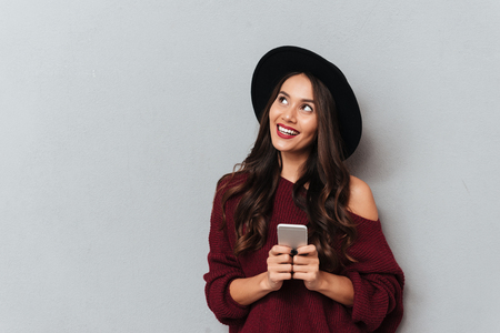 Photo pour Charming young woman in black hat and knitted sweater holding smartphone, looking aside, isolated on gray background - image libre de droit