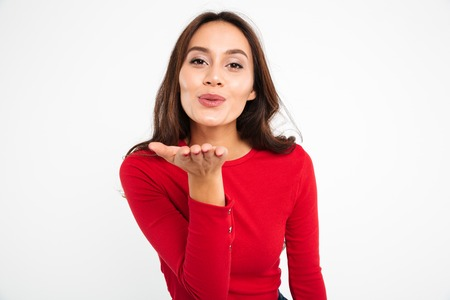Foto de Portrait of a lovely pretty asian woman sending air kiss while standing and looking at camera isolated over white background - Imagen libre de derechos