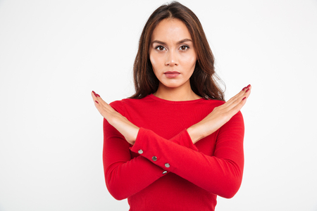 Foto de Portrait of a concentrated serious asian woman holding her hands crossed and looking at camera isolated over white background - Imagen libre de derechos